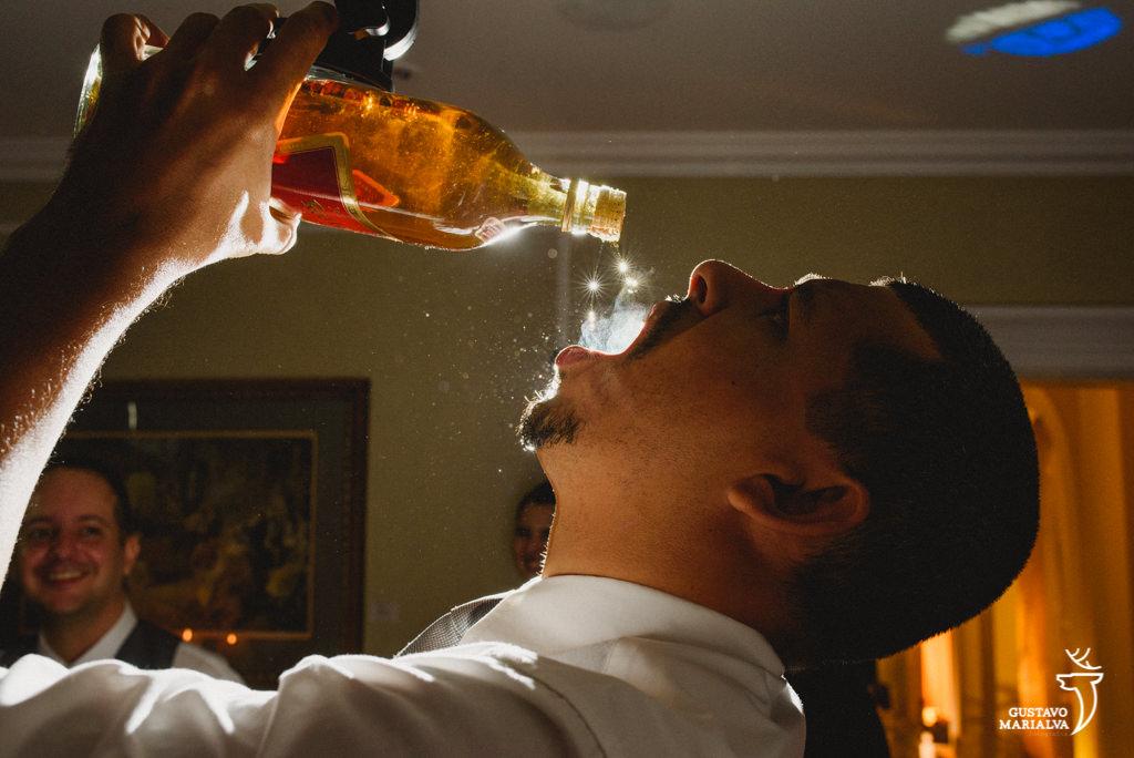 convidado bebendo whisky da garrafa