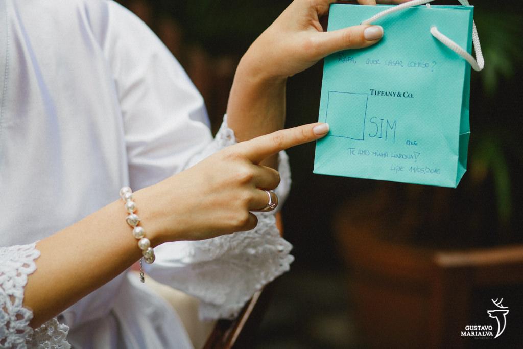Noiva recebendo presente do noivo da Tifany's durante o making of do casamento