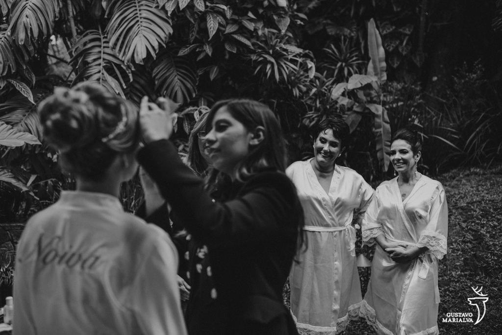 noiva sendo maquiada observada pela mã e sogra durante o making of do casamento