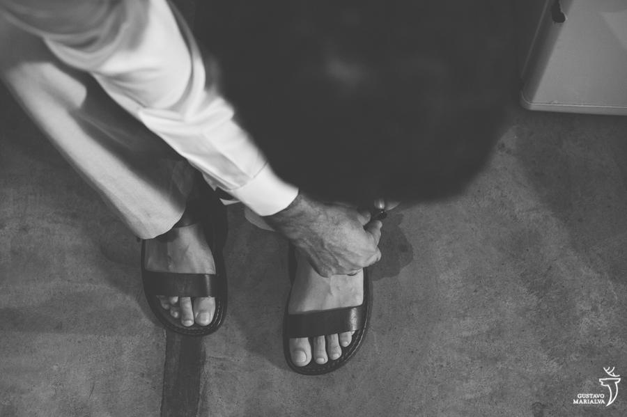 noivo colocando as sandálias no making of do casamento