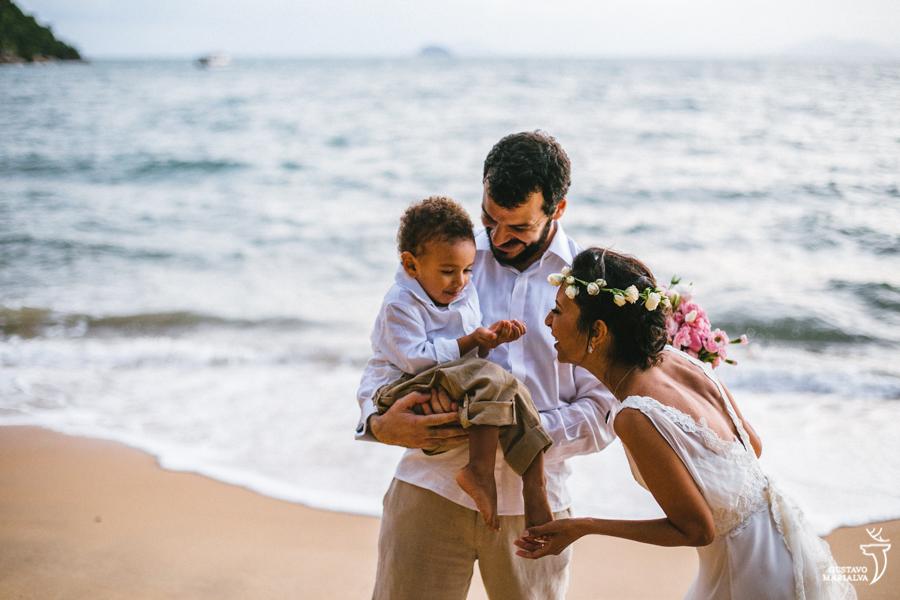 noivos brincando com filho na praia