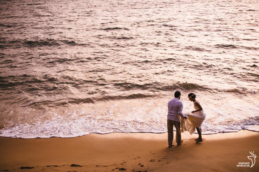 noivo ajudando a noiva a não molhar o vestido no mar
