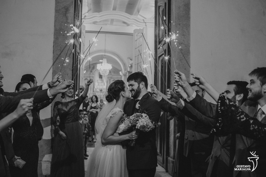 noivos se beijando na saída da cerimônia de casamento com os padrinhos segurando sparkles
