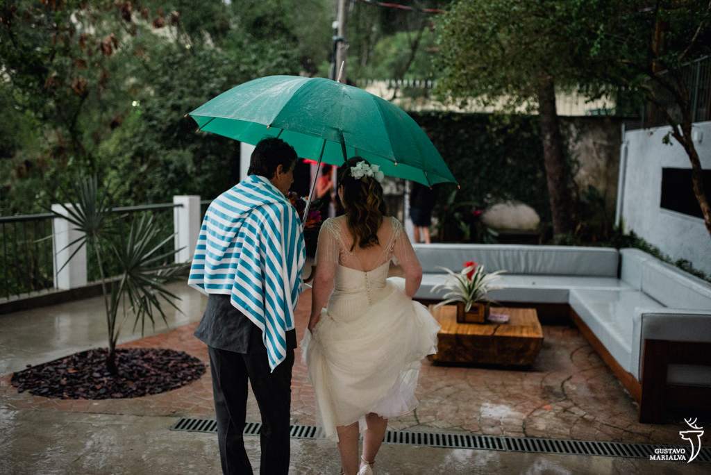 noiva indo para o casamento na chuva embaixo do guarda-chuva