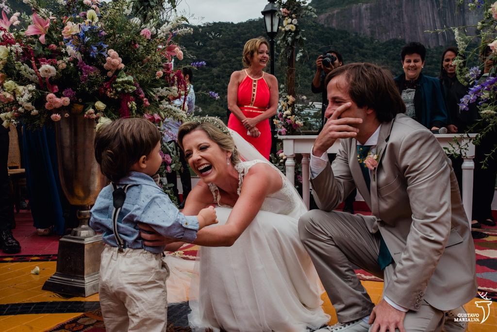 noivos emocionados e sorrindo com a entrada do filho na cerimônia de casamento