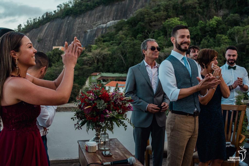 noivo e convidados aplaudindo a entrada da noiva na cerimônia de casamento