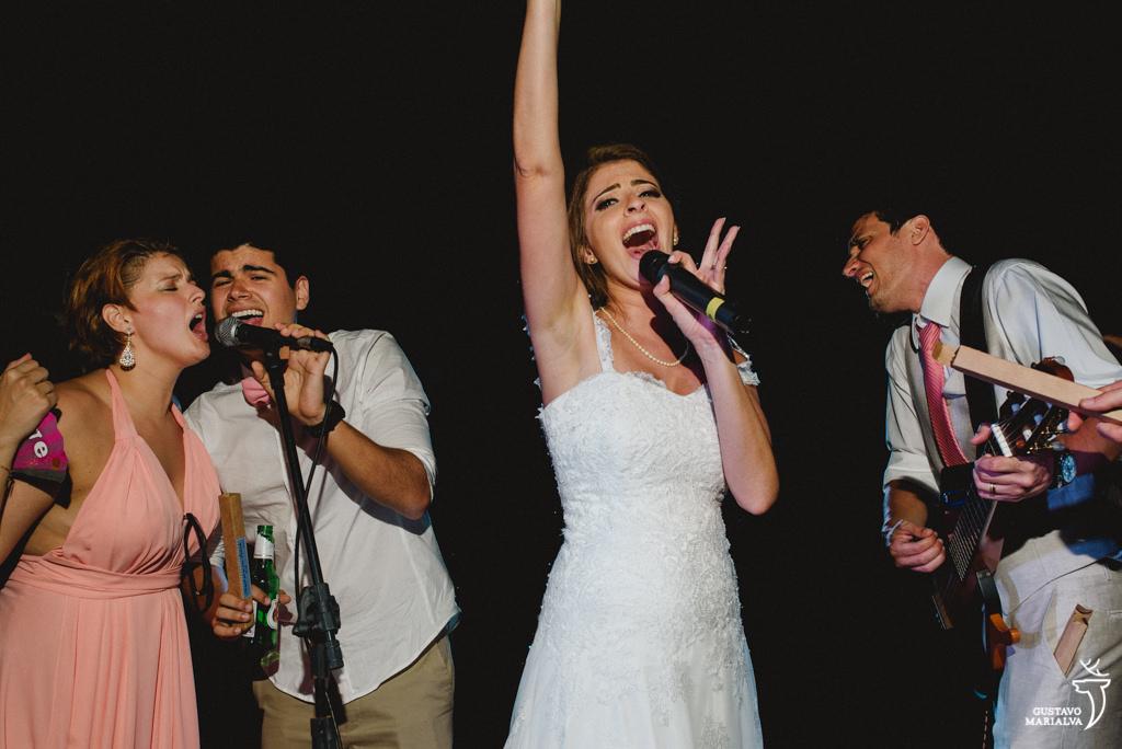 noiva cantando, noivo tocando violão e padrinhos fazendo backing vocal
