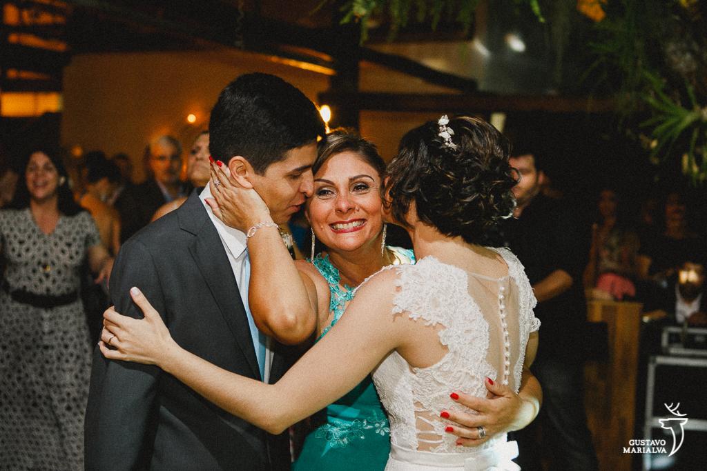 mãe da noiva emocionada recebendo abraço dos noivos