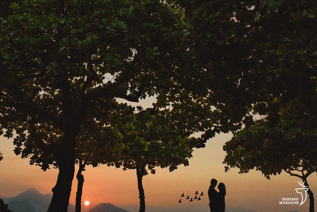 noivos namorando no por do sol durante book de casal