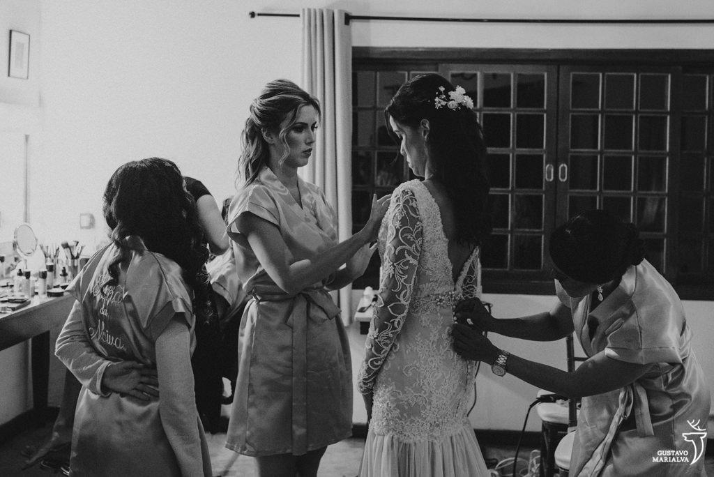 madrinha e mãe arrumando o vestido da noiva