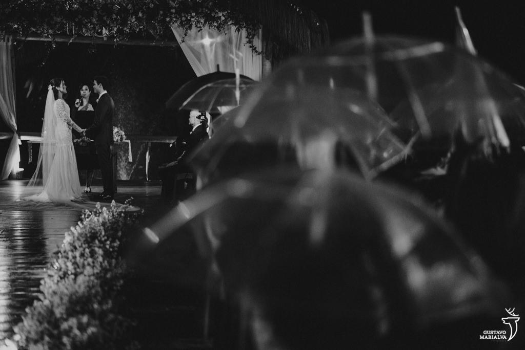 convidados se protegendo da chuva na cerimônia de casamento