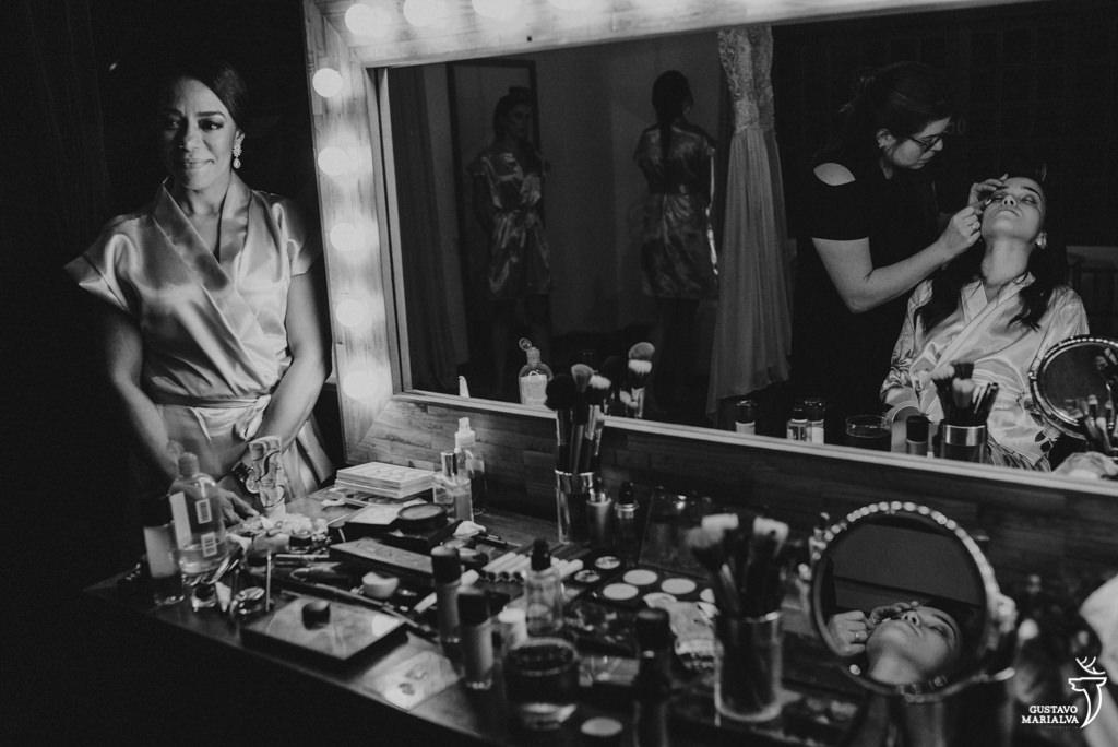 mãe emocionada observando a noiva se maquiando