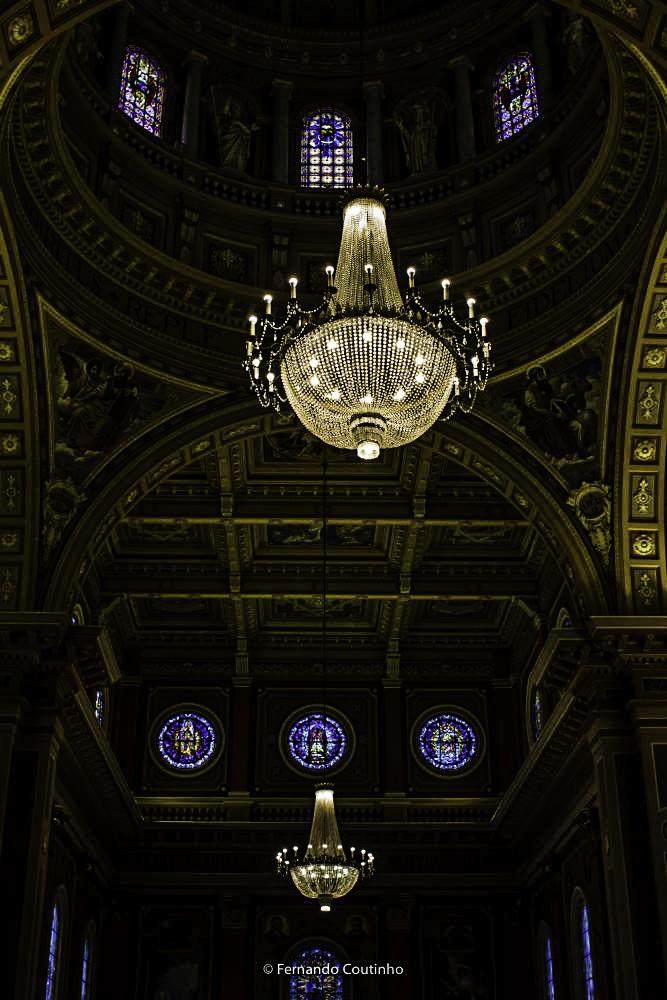 fotografia panoramica da igreja na penumbra destacando o lustre e os vitrais da basilica santo antonio de poadua em americana - sao paulo