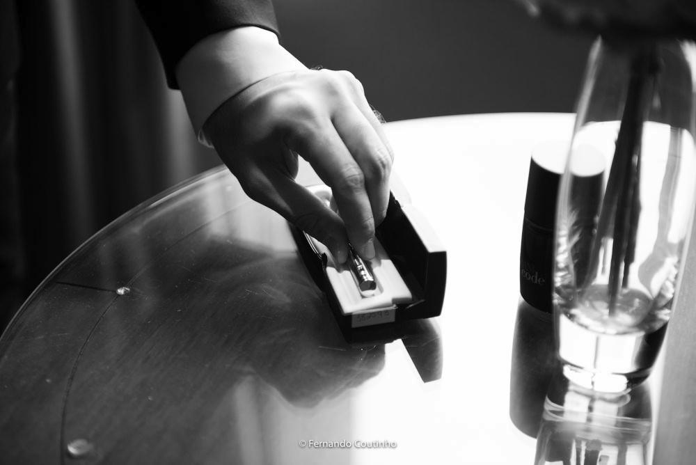 detalhe do noivo pegando a caneta que levara para o casamento religioso onde vai ter o casamento civil na igreja foto esta preto e branco