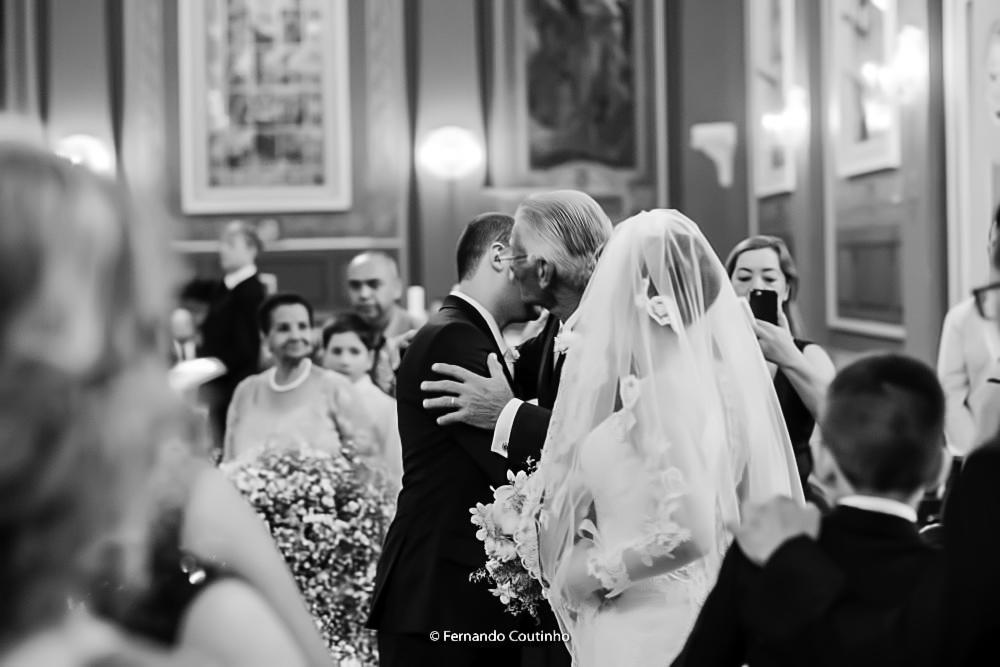 momento da entrega da noiva pelo paia da noiva ao noivo esta fotografia autoral de casamento foi feita pelo fotografo fernando coutinho fotografia preto e branco autoral