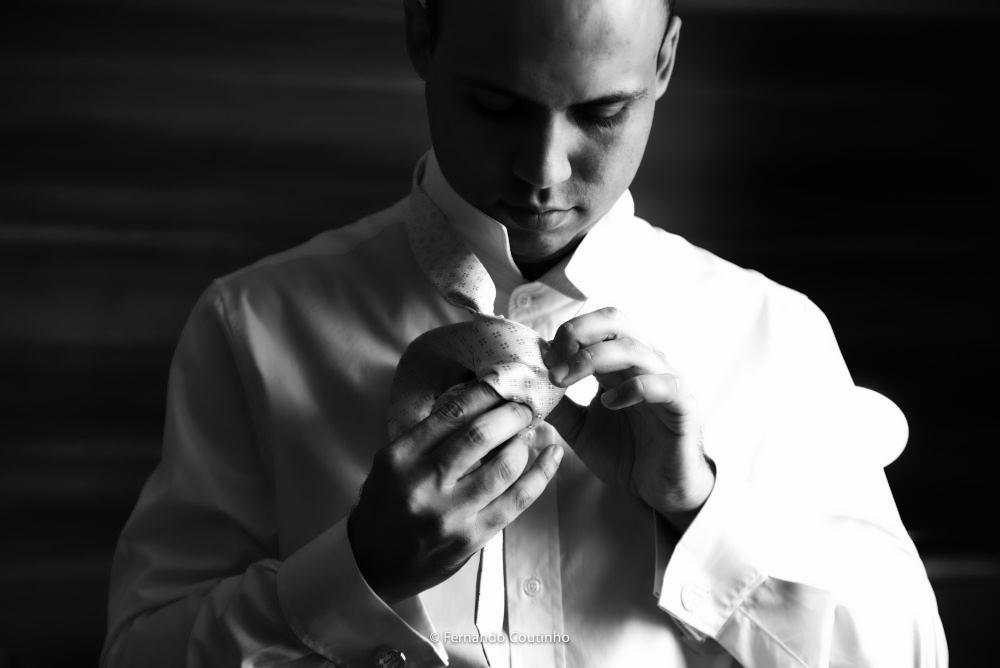fotografo autoral de casamento fotografia autoral casametno making of noivo arrumando no hotel da cidade aMERICANa sao paulo, noivo dando um no gravata para fotografia de casamento preto branco.