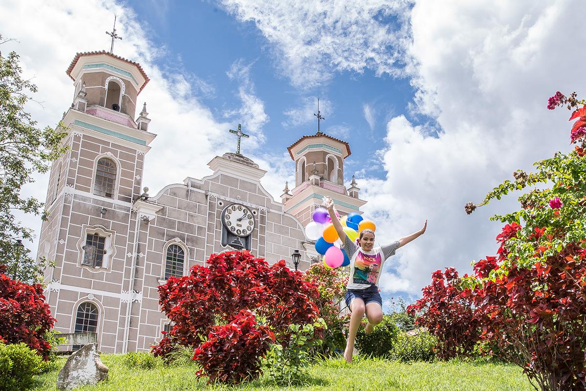 debutante com balões na frente da igreja