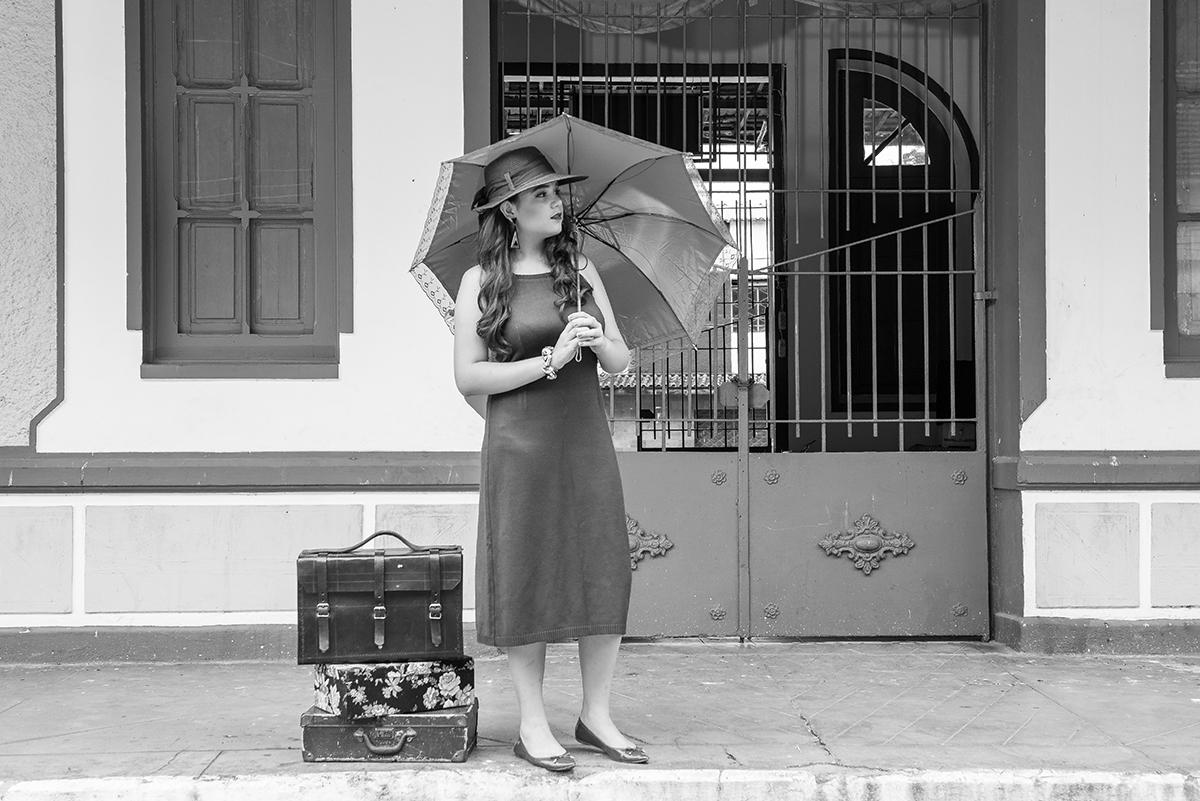 debutante com malas e guarda-chuva na estação