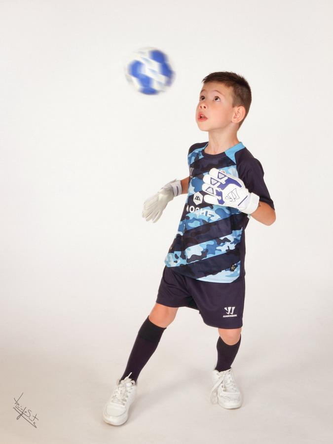 fotografia de estúdio miúdo a jogar futebol