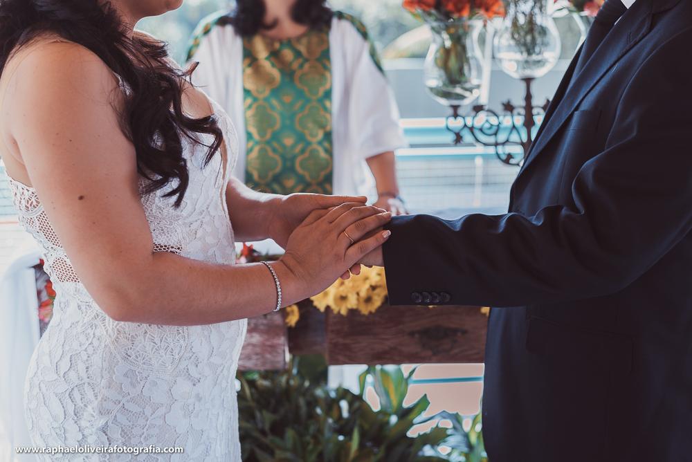 Noiva colocando as alianças no noivo