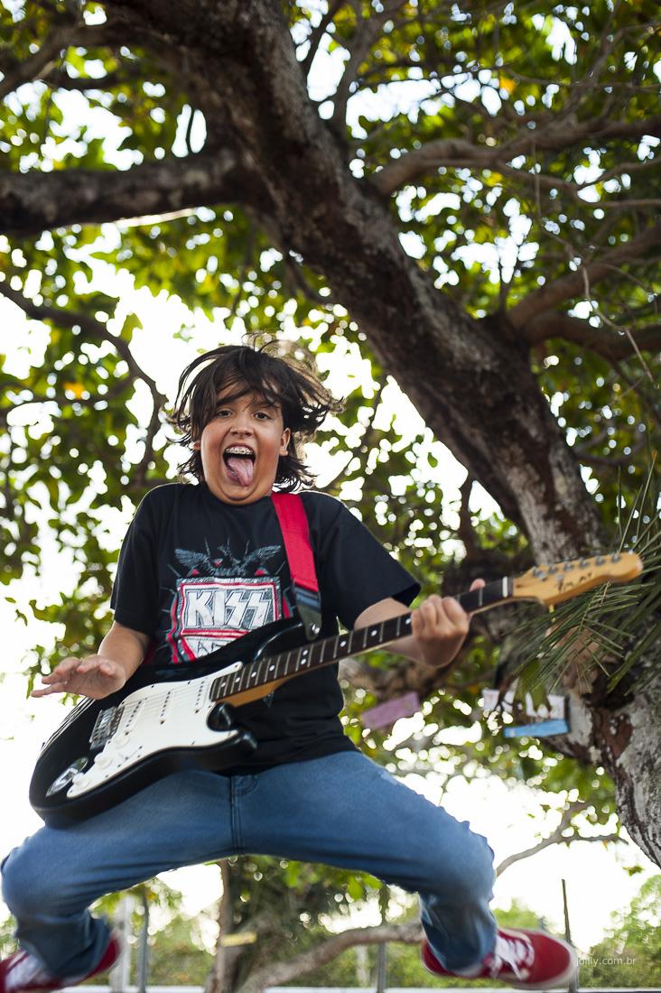 menino pulando com guitarra ensaio familia por rick joilly fotografia