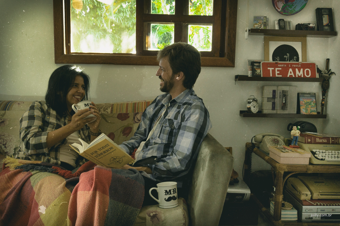 na sala de casa Paulo lê para Marta