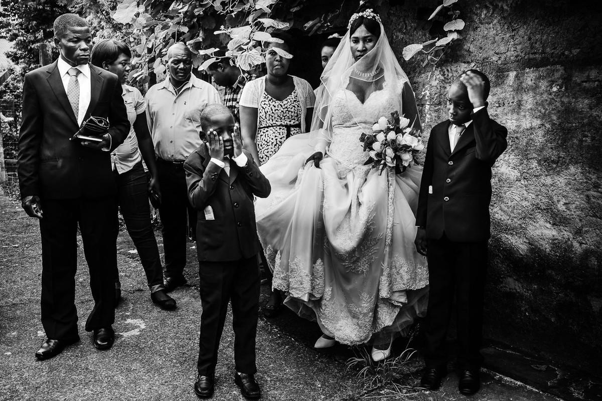 Em frente ao muro a noiva aguarda junto aos seus dois filhos haitianos e padrinhos para ir à igreja enquanto uma amiga ajuda a levantar o vestido