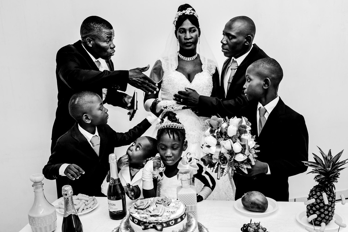 toasting the Haitian wedd next to the table is the bride with serene and deep semblance while the groom discusses with the godfather, the children look to each other and for the cake in front of them
