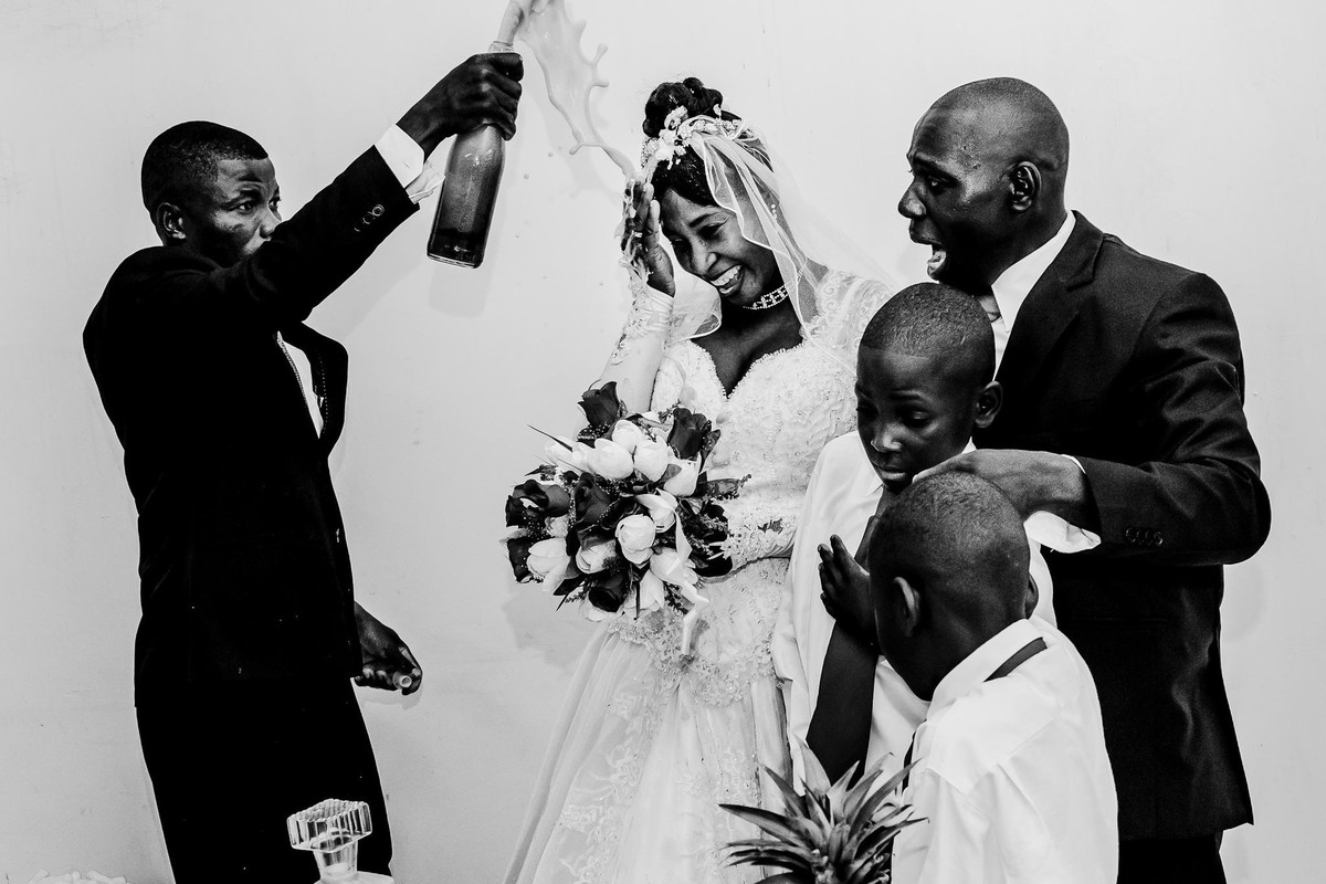 A special moment of the Haitian wedding in which the bride finally smiled while the godfather exploded the champagne in front of her next to the groom who looks at him terrified with the children