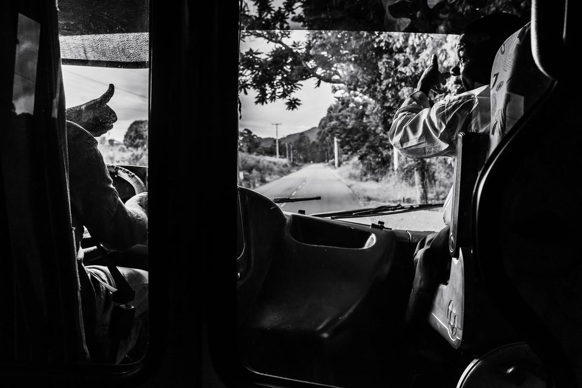 Dentro do ônibus está o motorista que acena com o polegar em direção ao passageiro sentado à sua direita que confirma o caminho a ser seguido