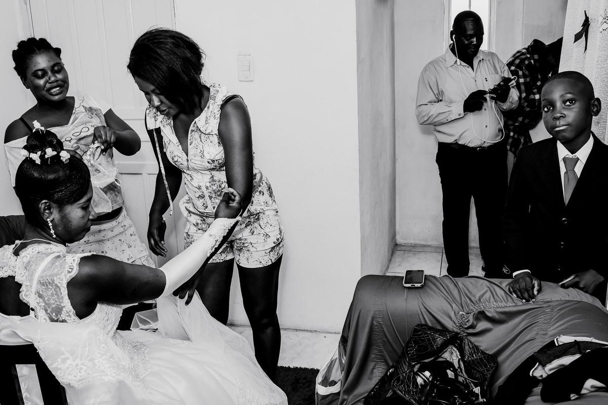 Na sala a noiva está se arrumando com a ajuda de duas amigas que estão lhe ajudando a fechar a luva. Perto do sofá uma criança haitiana encara a câmera, enquanto um adulto mexe no seu celular.