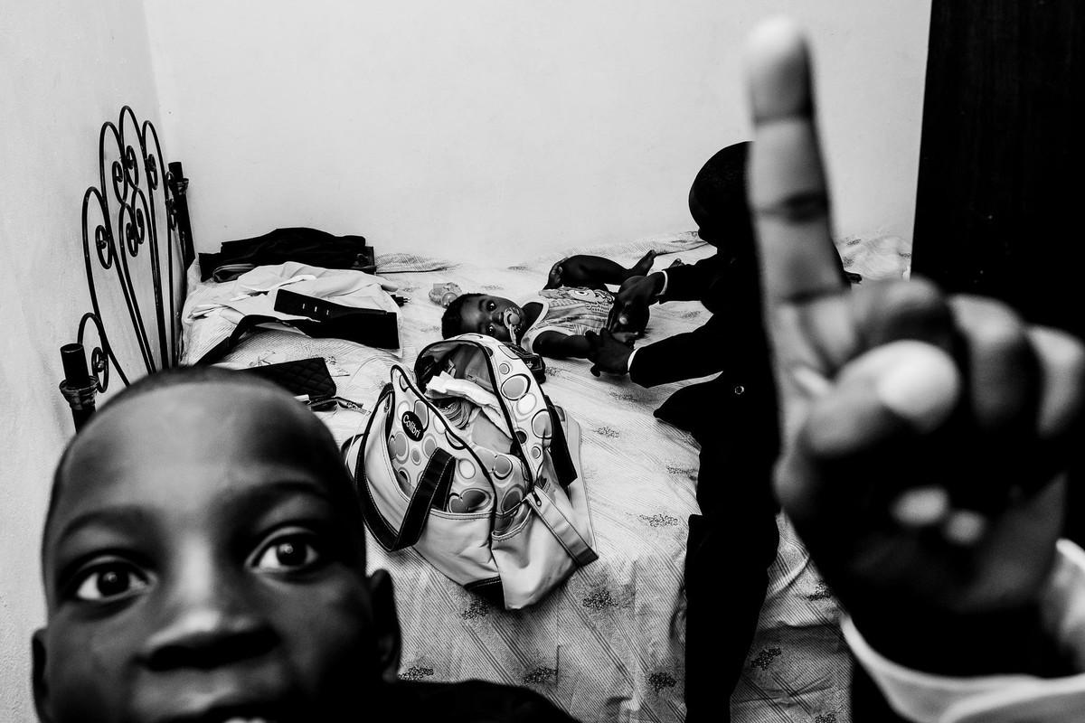 Menino haitiano em primeiro plano levanta seu dedo olhando para a câmera enquanto atrás dele tem outro menino ajudando um bebê a se vestir sobre a cama