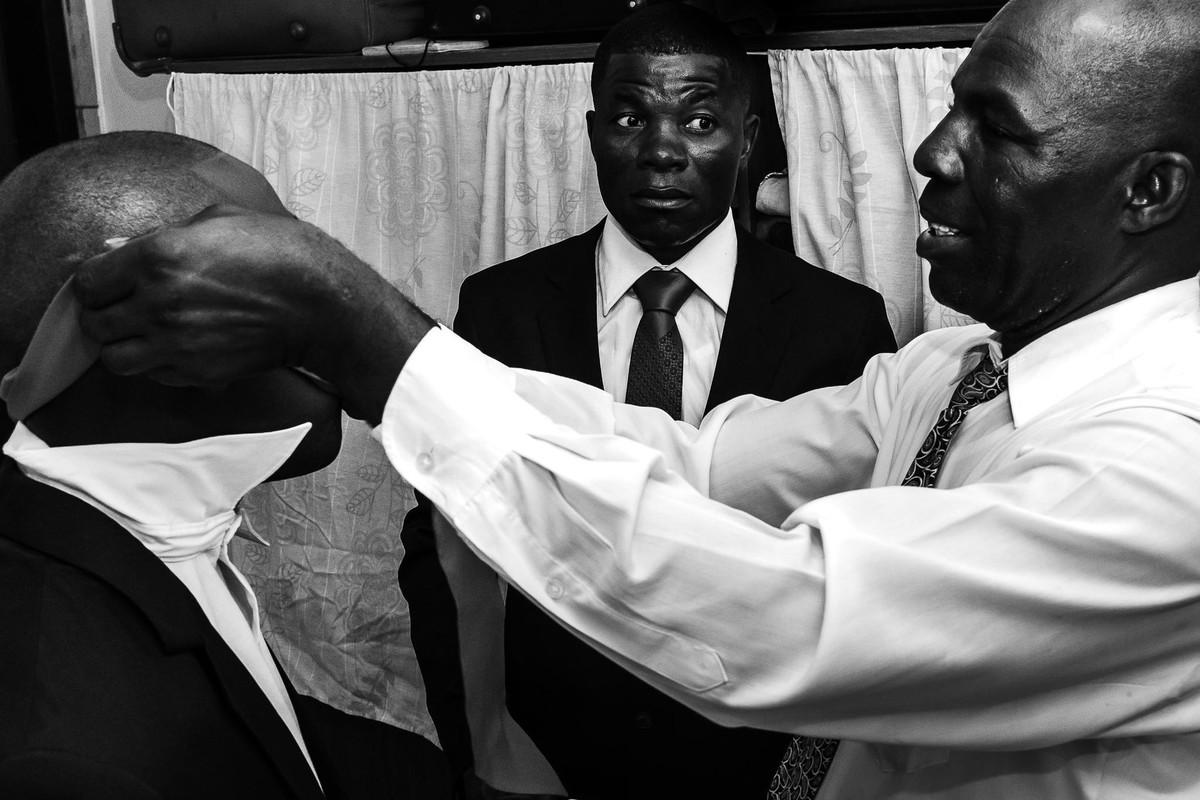 Padrinho está ajudando a colocar a gravata no noivo que ficou presa no seu rosto enquanto outro padrinho logo atrás deles olha assustado para o que está acontecendo