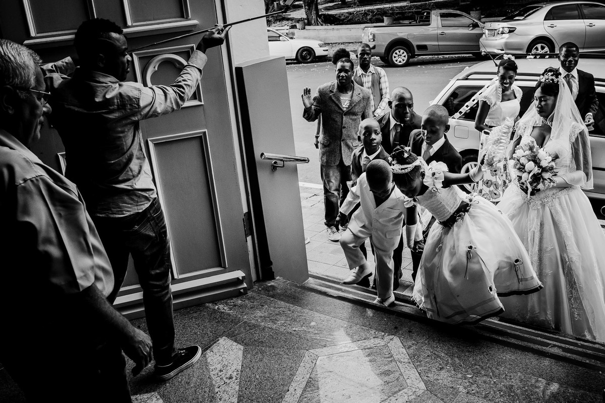 Os pajens e a daminha de honra sobem a escadaria da igreja de Estrela enquanto a noiva está atrás deles ao lado de amigos, tem alguém com pau de selfie dentro da igreja filmando a entrada