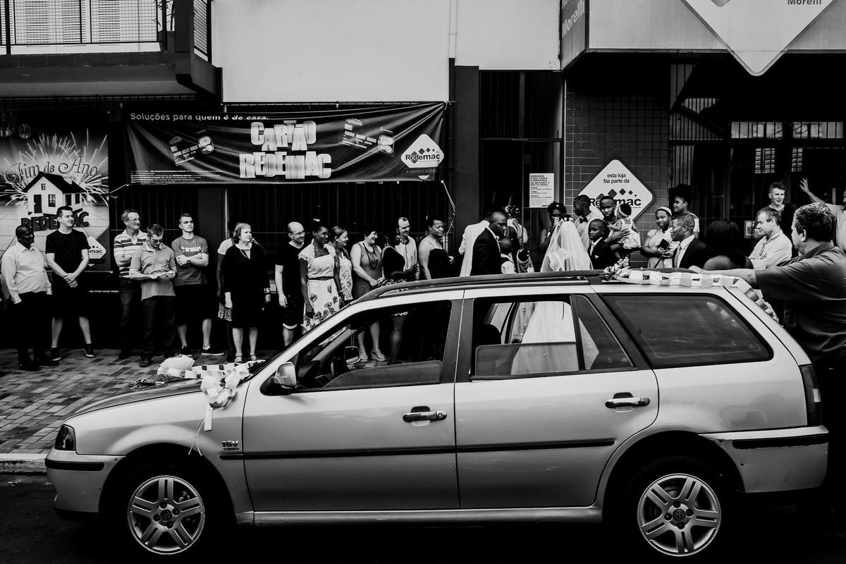 Convidados aguardam do lado de fora da loja Redemac e Morelli para recepção dos noivos enquanto o carro enfeitado que trouxe a noiva está estacionado em frente às mesmas