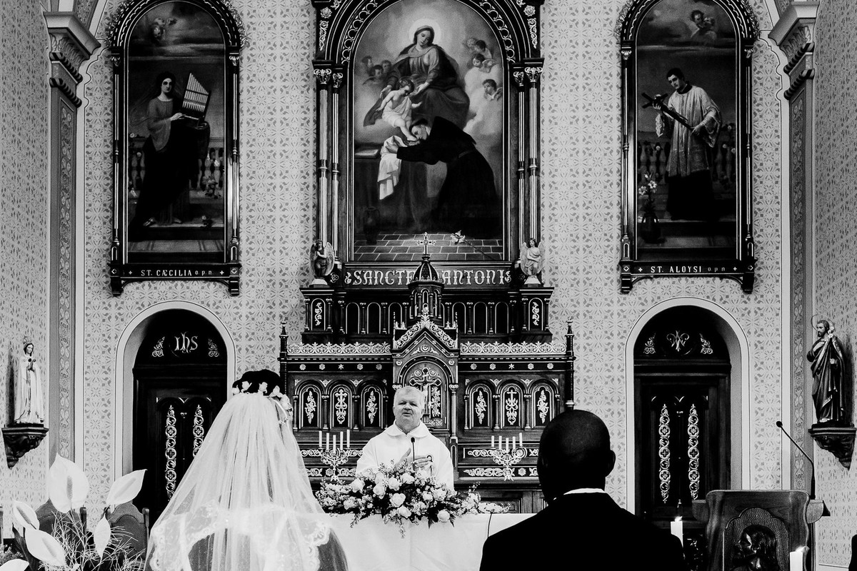 Os noivos estão lado a lado de costas para a câmera de frente para o altar da igreja matriz de Estrela decorada com painėis que compõem a cena em contraste com a pele branca do padre Azabido Ludwig