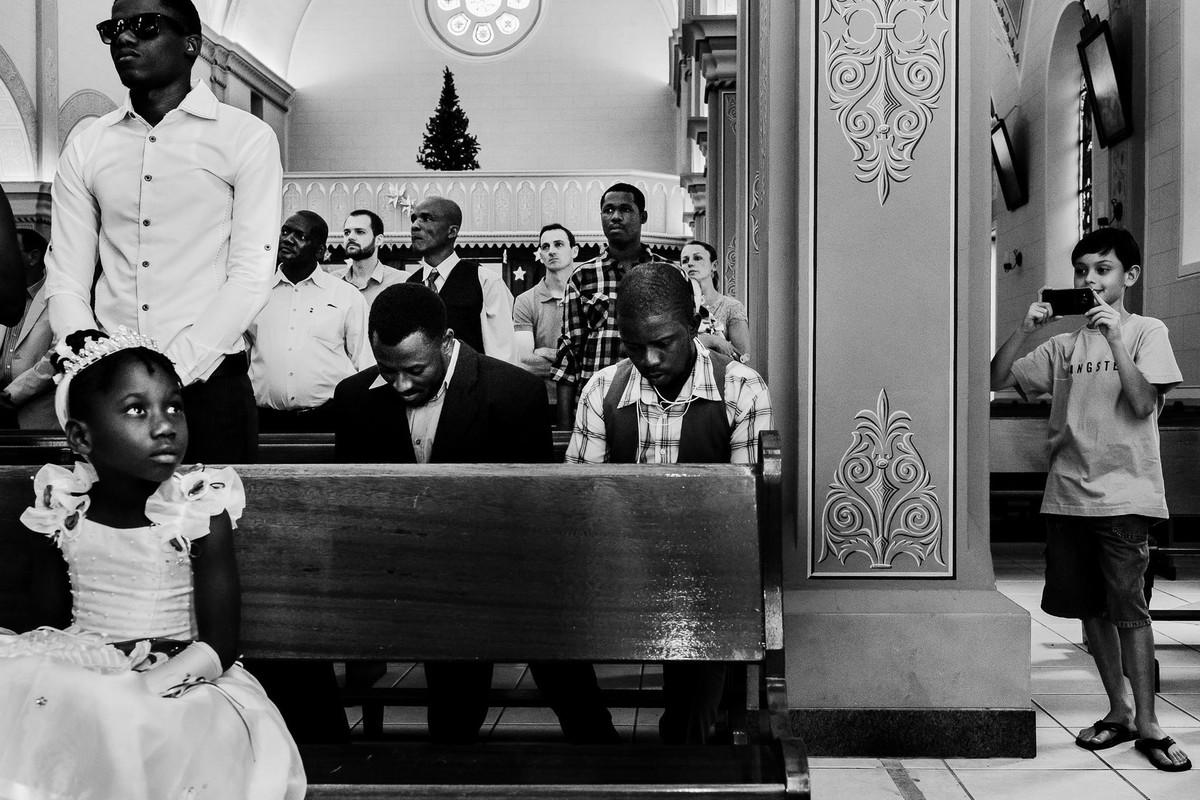 Enquanto o casamento haitiano está acontecendo é flagrada a presença de um menino branco registrando com seu celular numa das laterais da igreja enquanto aparecem demais haitianos sentados orando