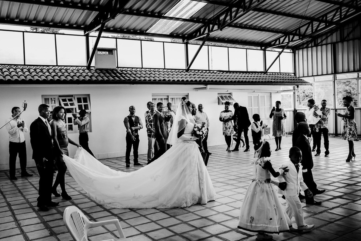 The guests cheerfully welcome the newlyweds Jack and Denise into the storehouse converted into a ballroom while the children walk in front of them