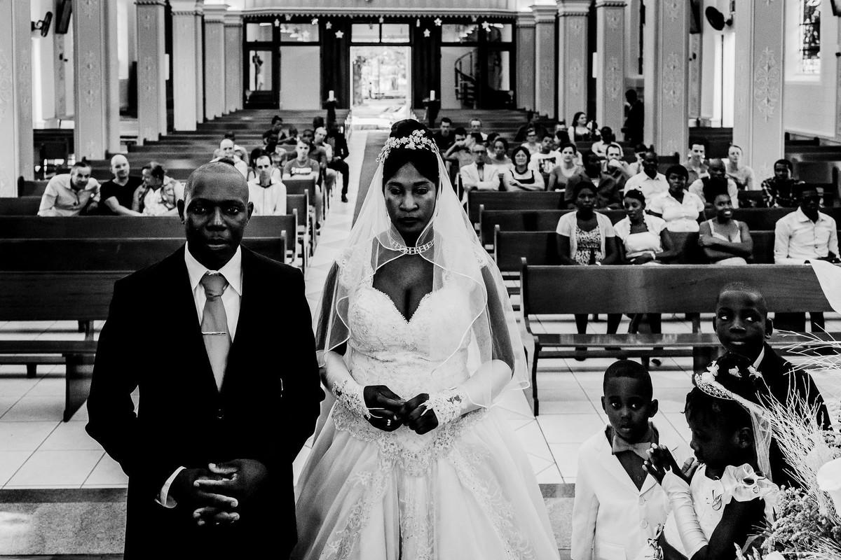 Os noivos haitianos estão em frente ao altar de pé cruzando as mãos em sinal de oração e ao seu lado estão os pajens e a daminha de honra e ao fundo os convidados sentados nos bancos da igreja