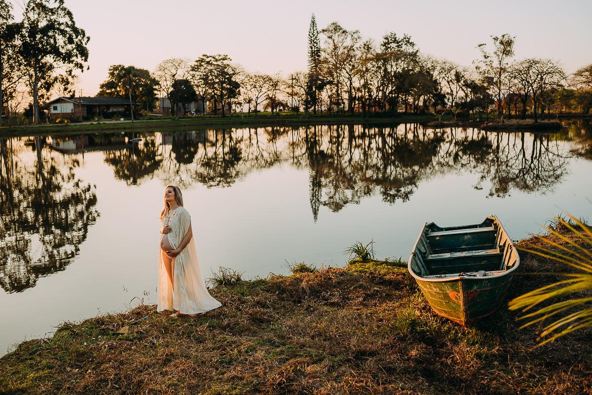 Grávida iluminada pelo sol durante ensaio de gestante à beira do lago.
