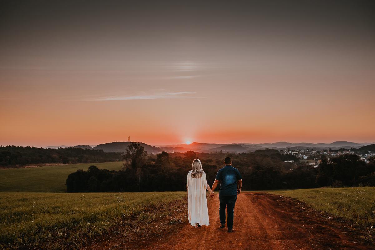 ensaio de gestante entre as colinas durante o pôr do sol em Estrela