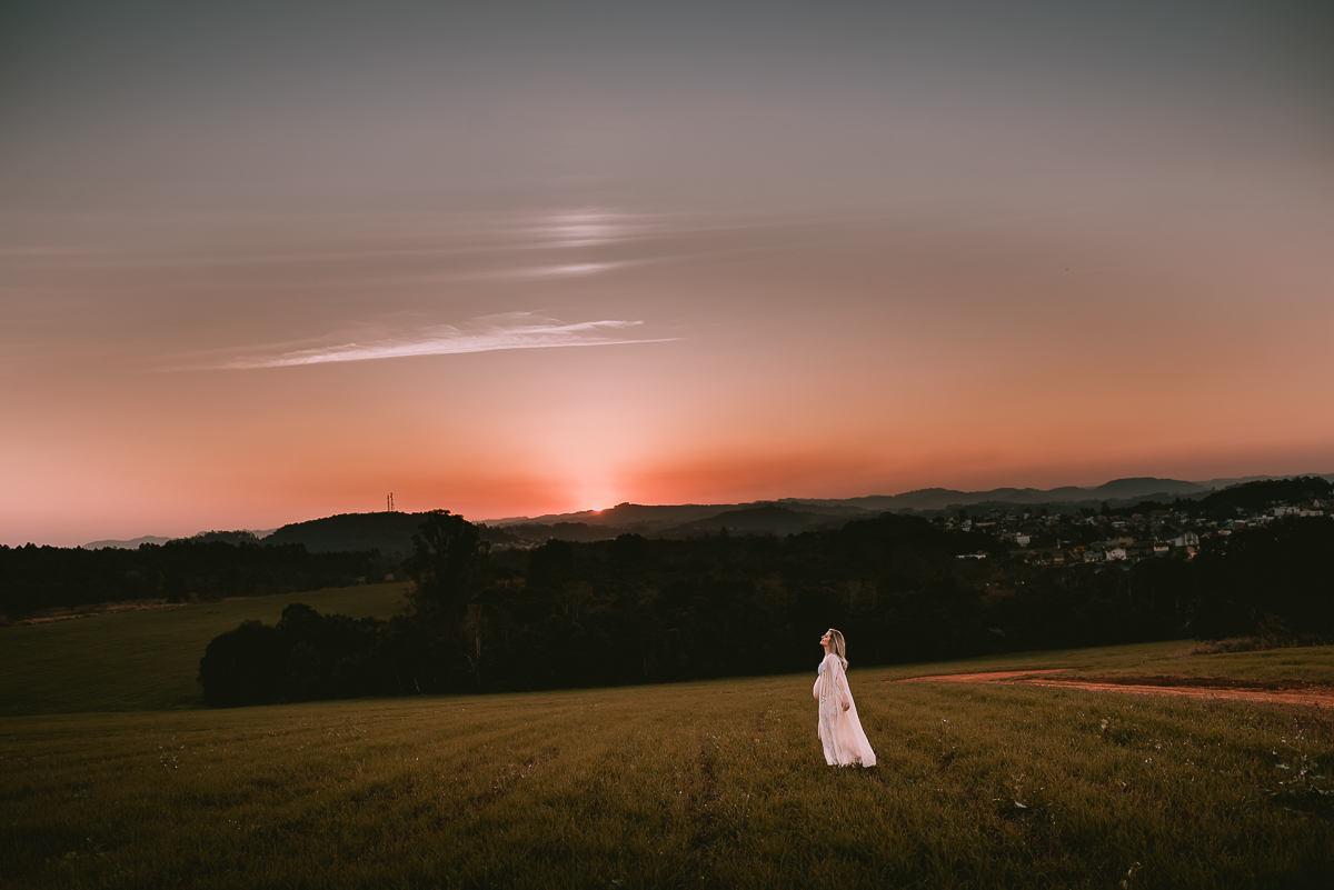 Gestante caminha no campo durante ensaio fotografico no fim da tarde