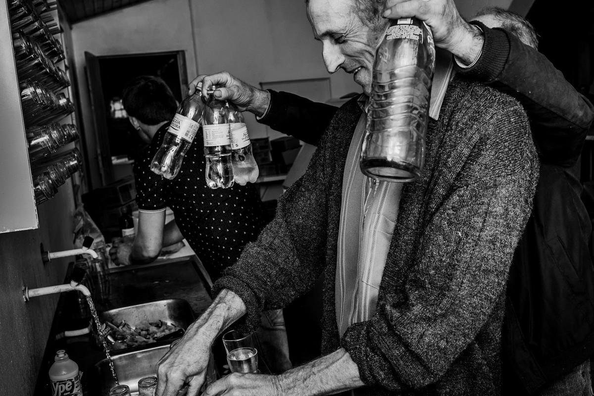 fotografia documental em preto e branco registra cena engraçada de homens na cozinha lavando a louça