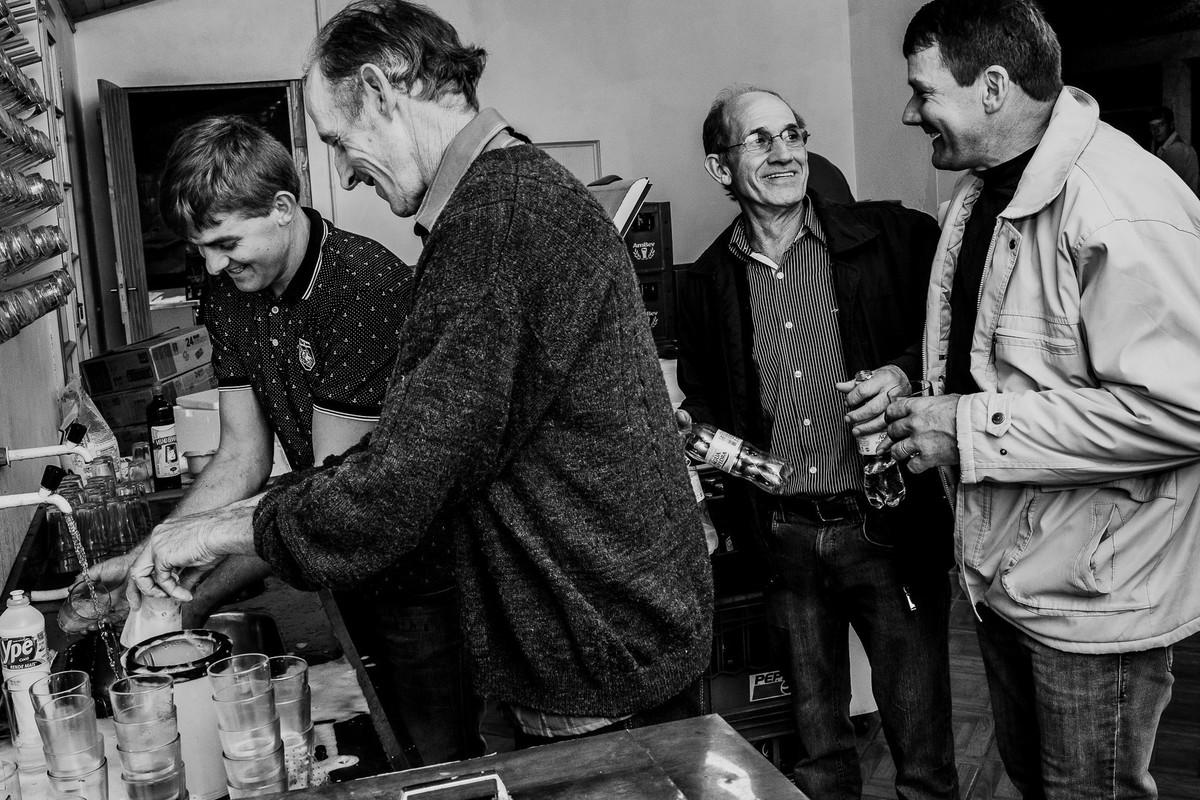 foto em preto e branco de homens se divertindo na cozinha lavando a louça