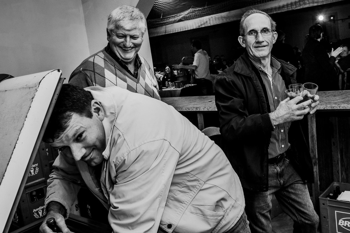 cena engraçada de homem mostrando a lingua junto a seus amigos na copa do salao de festas