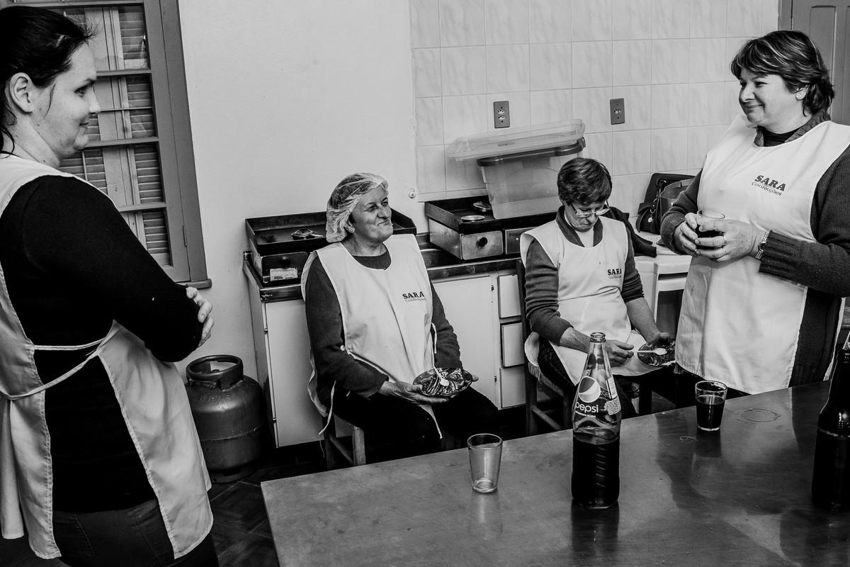 Mulheres no intervalo fotografadas na cozinha do salão de festas no interior do RS