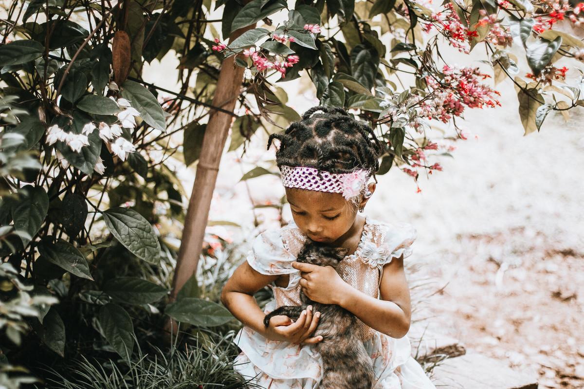 Ensaio fotográfico fofo de criança haitiana brincando com filhote de gato