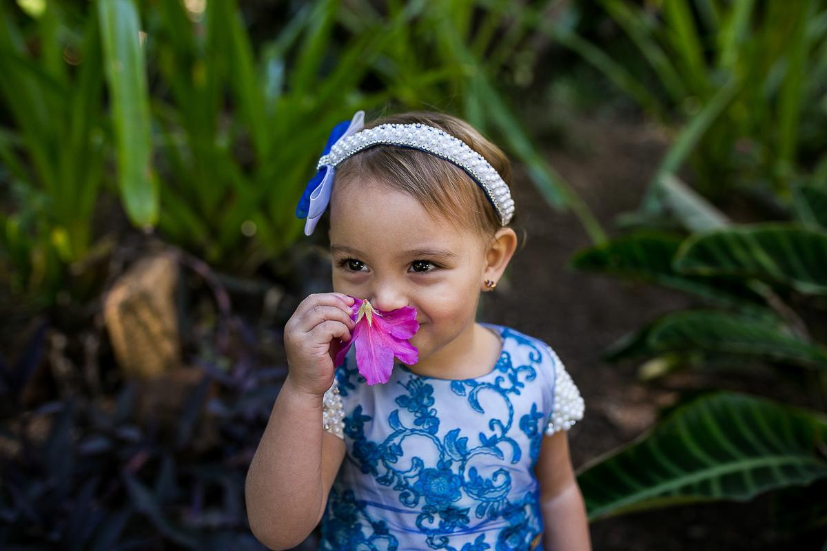 nina cheirando flor