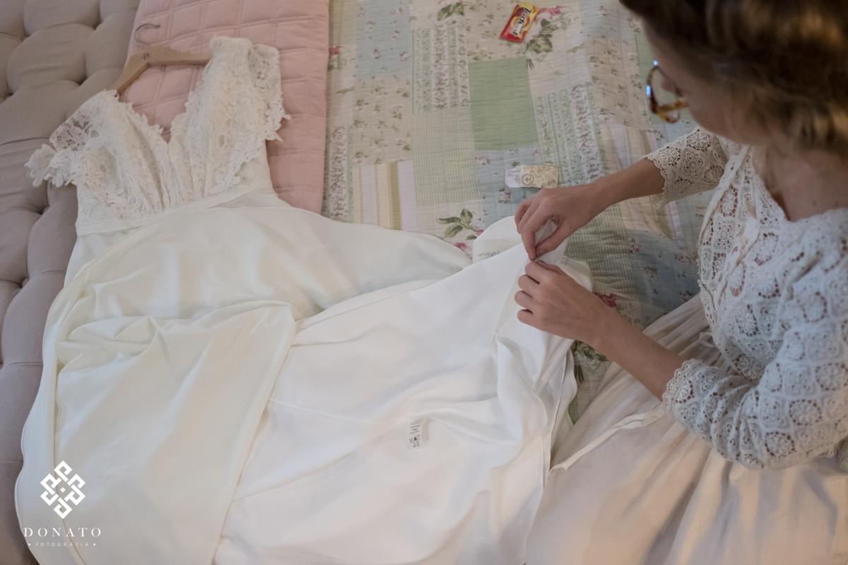 Noiva arruma os detalhes da borda do vestido, costurando com uma linha e agulha.