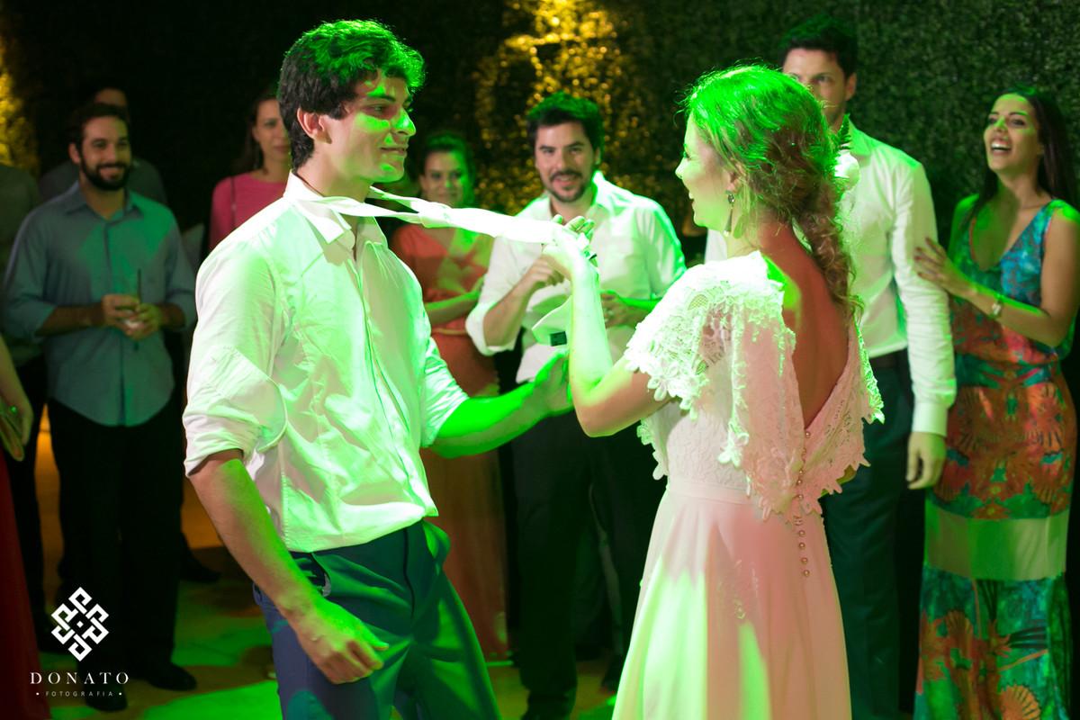 Noiva dança com o noivo, agarrando ele pela gravata.